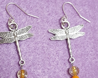 Silver dragonflies with orange and yellow tail