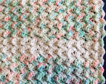 Crochet baby blanket in pinks and greens with white stripes