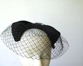 Glamour vintage 60s black fascinator hat with a black velvet, large bow and double net top.One size fits all.