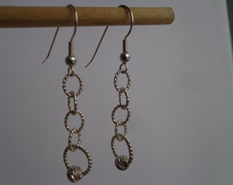 Dangling twisted silver wire earrings.