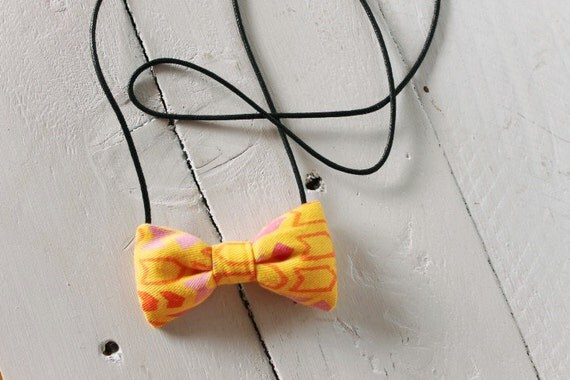Bow necklace >> Yellow, pink, orange patterned arrow bow on black cord >> Brisbane