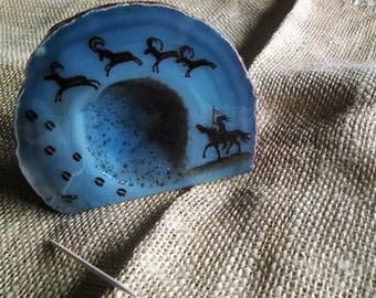 """pictograph  painting of Rams and an Indian brave on horseback, on a Geode half Agate,  size 4"""" wide gray/brown agate with crystal center"""