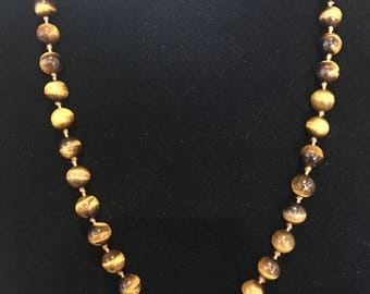 This is a vintage hand knotted tiger eye bead necklace.