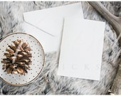 Vertical Blank stationery invitation holiday christmas card mockup stock photo on gray fur with polkadot plate and gold pinecone and antler