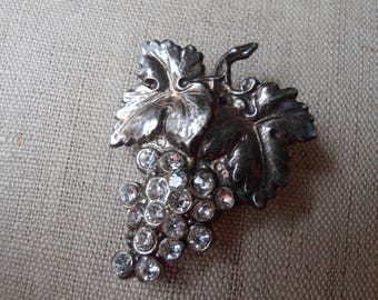 A vintage pin or brooch in the shape of a bunch of grapes