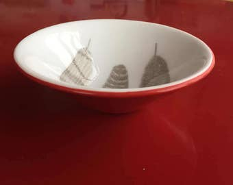 Small red and white fused glass bowl with feather detail.