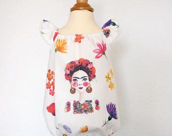 Frida Kahlo Baby Romper. Sizes from 0 to 3 years gathered neck and pompoms on the sleeves. Fabric printed canvas flowers and Frida Kahlo