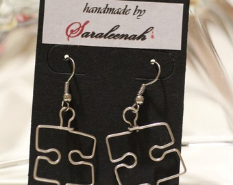 Silver wire wrapped handmade earrings in the shape of puzzles