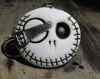 White round skull with a saw in his eye. Keychain or pendant