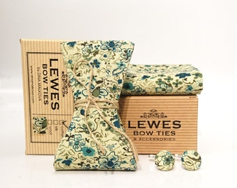 A set of men's self tie bow tie, pocket square and a pair of cuff links made from ivory cotton fabric with teal and olive green floral print