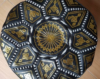 Moroccan leather pouf in black, white, and gold