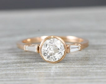 White sapphire and diamond engagement ring handmade in rose gold with baguette accent stones