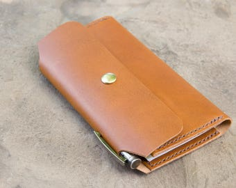 Leather checkbook cover with pen holder in cognac