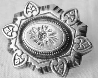 A vintage silver brooch  with floral central design and six heart shaped petals. Victorian language of flowers