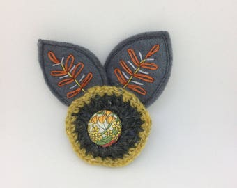 Crochet and felt flower brooch with embroidery detail leaves and liberty fabric button center.