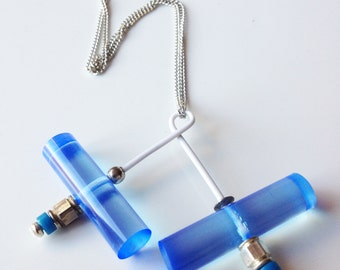 Sky, contemporary necklace in a tube of bright blue acrylic