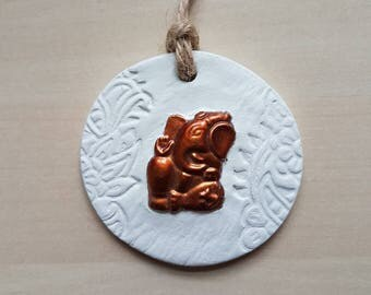 Hanging white clay ornament with bronze Ganesh. Floral henna style design. Hindu God. Ethnic. Twine to hang. Spritual. One of a kind.