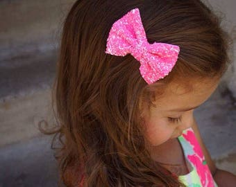 Pink bright chunky glitter bow on an alligator clip