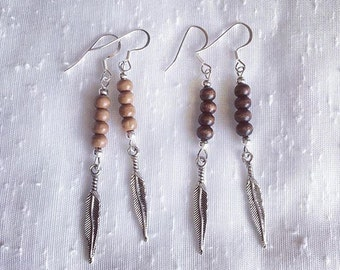 Dangle earrings, wood beads and feather charms.