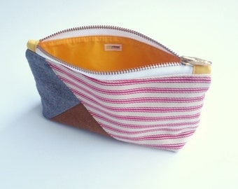 Red and white stripes with brown, grey and gold. Zipper pouch for toiletries, made with waterproof lining.