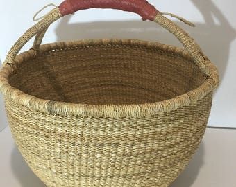 A natural bolga basket with a leather handle