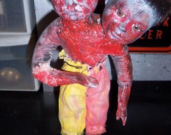 2 headed clown burnt in a fire.  (doll)