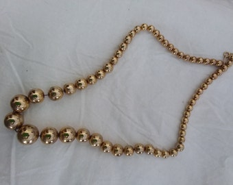Gold bead or beaded necklace, large beads, graduated to small beads. Chain is metal. Estate costume jewelry