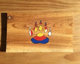 Bear paw with Colorado flag colors on stained cedar
