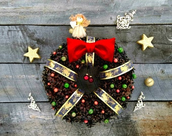 Christmas wreath made of natural Siberian cones with a golden ribbon and a red bow