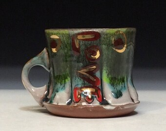 Love gold mug with red and green with copper black glaze over top white inside