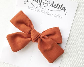 Rust fabric tied alligator clip bow
