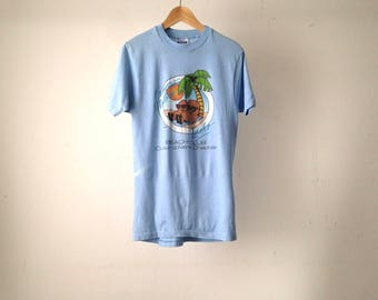 vintage HOLIDAY tourist COUCH POTATO Coeur d'Alane, Idaho faded blue tropical vacation t-shirt top