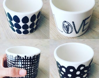 mini porcelain cups screen printed and hand painted various patterns and text.