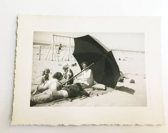 vintage black and white photo of women under an umbrella on the beach
