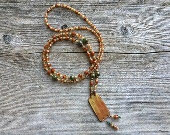 Long burnt orange necklace with enameled disc centerpiece