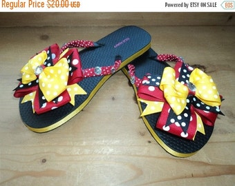 Red, yellow, and black over the top bow flip flops