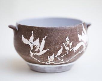 White magnolia. Dark brown clay tureen.