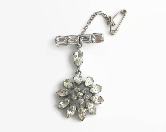 Rhinestone flower brooch with dangling flower suspended from bar with 4 rhinestones, rhodium plated silver setting, safety chain, 1950s