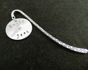 Hand stamped personalized disc, with two names and a heart (straight style), on a bookmark.