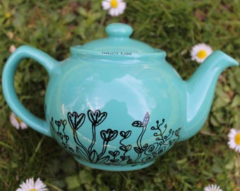Hand drawn small turquoise porcelain teapot with flowers and leaves pattern florals botanicals