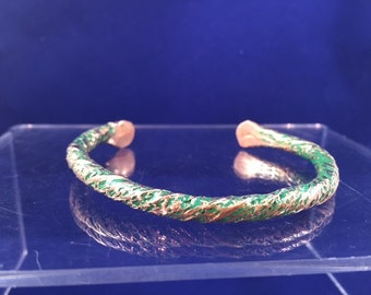 "1/4 "" solid copper bracelet, fits most wrists, green patina in the background"