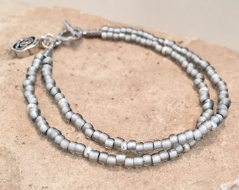 Gray double strand seed bead bracelet with Hill Tribe silver rondelle and tube beads with a Hill Tribe silver toggle clasp and flower charm
