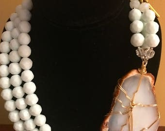 Handmade Necklace made with white faceted glass beads, featuring a slab crystal and a large circular clasps
