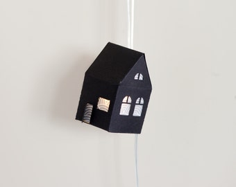 String of lights decorated with 10 black houses in paper