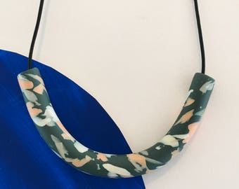 Modern marble effect necklace, a long curved bead made from polymer clay.
