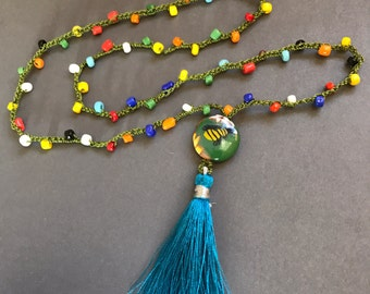 Gardener's bee necklace with bright blue tassel