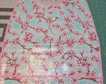 Pink blossoms on blue sky in springtime. Oilcloth adult bib with crumb catcher pocket makes for easy clean-up.  Snap closure good coverage