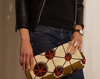 Stylish clutch in geometrical Vlisco print in brown, ivory, maroon, and red