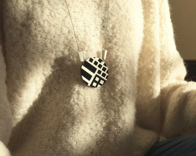 Black and white geometric pendant in white and patent black leather with two vintage lucite beads