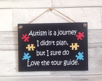 Autism quote, black wooden sign, jigsaw pieces, family life, colourful jigsaw pieces.